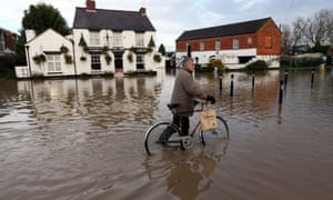 A pedestrian pushes his bike through flood water in Tewkesbury on 26 November 2012.
