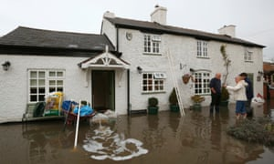 Residents speak outside a flooded house, close to the River Trent in Willington.