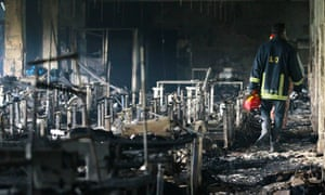 A firefighter inspects the Tazreen Fashion garment factory in Ashulia, Bangladesh, following a fire