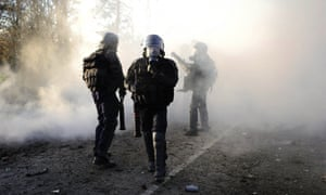 Riot police walk amid tear gas during clashes with protestors against a project to build an international airport Notre-Dame-des-Landes, western France, during a demonstration against the project.