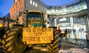 People walk past a tractor with a sign reading '' no future without farmer'' in front of the EU Parliament at Place du Luxembourg, on the second day of a protest against falling milk prices in Europe, on November 27, 2012 in Brussels.