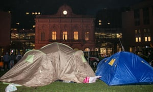 People stand by tents set up by dairy farmers at Place du Luxembourg, on the second day of a protest against falling milk prices in Europe, on November 27, 2012 in Brussels.