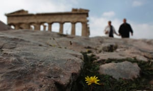A couple walks in front of the Parthenon temple at the Acropolis hill in Athens November 27, 2012.