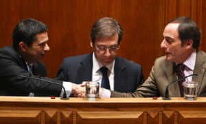 The Portuguese Minister of State and Finance Vitor Gaspar (L) greets the Minister of State and Foreign Affairs Paulo Portas (R) accompanied by the Prime Minister Pedro Passos Coelho (C) during the parliamentary debate on the State budget for 2013 today.