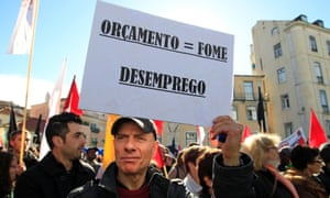 """A man holds a sign reading: """"Budget = hunger, unemployment"""" during an anti-austerity protest in front of Portugal's parliament in Lisbon November 27, 2012."""