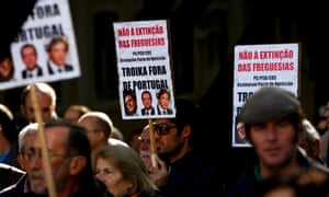 Protesters hold posters with the words 'No to the extinction of the Parish... Troika out of Portugal' and shout slogans during a protest near the Parliament, on the last day of discussion in Parliament of the draft State budget for 2013, in Lisbon, Portugal, 27 November 2012.