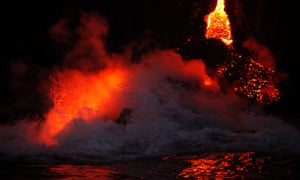 Waves crash over lava as it flows into the ocean near Volcanoes National Park in Kalapana, Hawaii. A volcano on Hawaii's largest island is spilling lava into the ocean, creating a rare and spectacular fusion of steam and waves.