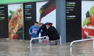 Daniel Roberts and Courtney Cox help nine-year-old Skye Thomas take refuge in a Co-Op shopping trolley in St Asaph on 27 November 2012.