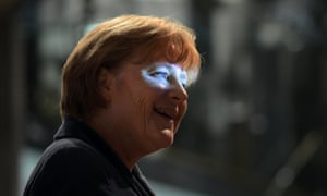 German chancellor Angela Merkel smiles as she is illuminated by a beamer as she arrives for a ceremony of the association of welfare organizations BAGFW in Berlin.