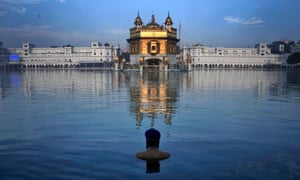 An Indian Sikh devotee takes a holy bath in the sacred pond of the Golden Temple during the birth anniversary of Guru Nanak, in Amritsar, India.