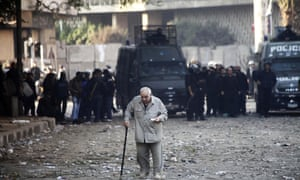 An Egyptian man slowly walks away as demonstrators and riot police clash near Tahrir Square in Cairo. Police fired tear gas into Cairo's Tahrir Square, where several hundred protesters spent the night after a mass rally to denounce President Mohamed Morsi's assumption of expanded powers.