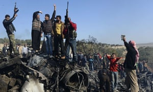 Syrian rebels celebrate on top of the remains of a government fighter jet which was shot down at Daret Ezza. Syrian rebels captured the pilot manning the fighter jet.