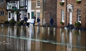 People walk through waters surrounding buildings as residents of Old Malton begin to deal with the aftermath of the recent floods. Fire crews continue to pump large amount of surface flood water away from overflowing drains that have been threatening many properties in the area.