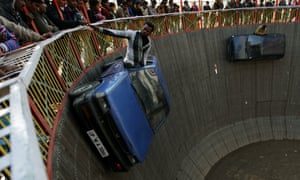 Indian performers ride in cars inside a makeshift wooden cylindrical wall of death' structure, during the annual farmers fair at Shama Chak Jhiri, Jammu.  Farmers in huge numbers from all over India gather to pay tribute to the Samadhi or tomb of legendary farmer Baba Jit Mal, popularly known as Baba Jitto who sacrificed his life for the liberation of the farming community.
