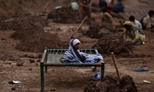 A Pakistani child sits on a bed wrapped with a blanket to avoid the cold, while her mother works in a brick factory on the outskirts of Islamabad, Pakistan.