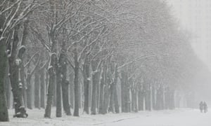 Two people brave the weather to walk along a tree-lined snow-covered avenue  in front of Moscow's University building. Russia.