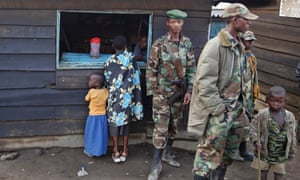 A woman and child stand next to M23 rebel fighters as they prepare for withdrawal from Karuba, west of Goma. Rebels in the Democratic Republic of Congo said they would pull out of the eastern city of Goma in an apparent stalling of their drive to 'liberate' the whole country.