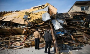 Men survey the damage caused by Hurricane Sandy in the Ortley Beach area of Toms River, New Jersey