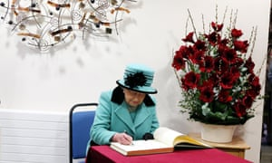 The Queen signs the visitors book during a visit to Thames Hospicecare in Windsor to mark the hospices's 25th anniversary.