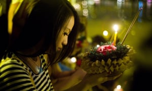 A woman prays before launching a floating lantern to celebrate Loy Krathong in Chiang Mai, Thailand.