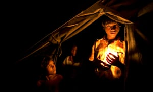 A child holds a candle at a crowded internally displaced persons camp on the outskirts of Sittwe, Burma.