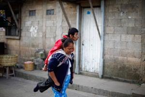 24 hours in pictures: Catalina Garcia piggybacks her son in Tierra Nueva