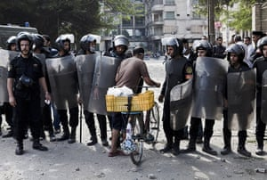 24 hours in pictures: An Egyptian man is let through a police line with his bicycle