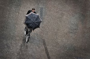 24 hours in pictures: A man rides a bicycle on a snowy day