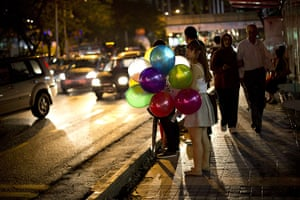 24 hours in pictures: A girl holds a bunch of balloons as she waits at a bus stop
