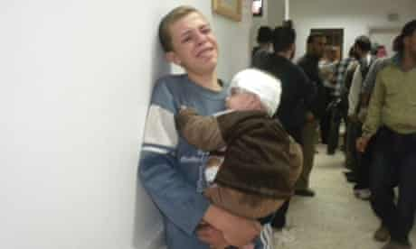 A boy carries his injured brother at a makeshift hospital after a Syrian Air Force fighter jet loyal to President Bashar al-Assad reportedly fired missiles at Houla, near Homs, on 7 November.