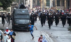Protesters run during clashes with police near Tahrir Square