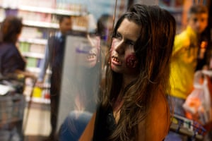Zombie walk: A girl dressed as a zombie looks into a shop window