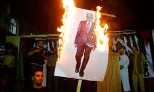Palestinian refugees burn an image of Mahmoud Abbas
