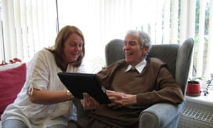 An elderly man looking at an ipad with a carer