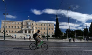 A cyclist drives in front of the Greek Parliament in central Athens, Monday, Nov. 5, 2012.