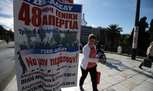 A woman passes a labor union banner calling for 48 hour strike at Syntagma square in central Athens, Monday, Nov. 5, 2012.