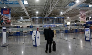 A passenger looks at an announcement board inside the Athens Eleftherios Venizelos airport a few hours before a work stoppage by flight controllers begins in Athens November 6, 2012.