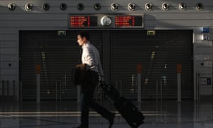 A passenger walks in front of a closed entrance of a suburban railway station at the Athens Eleftherios Venizelos airport in Athens November 6, 2012.