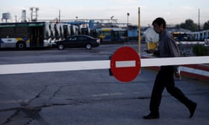 A bus drivers walks past buses that are parked at a depot in Athens during a 48-hour nationwide general strike on Tuesday, Nov. 6, 2012.