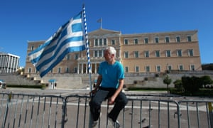 A protester holds a Greek flag in front of the Greek parliament during a rally on the first day of the 48-hour nationwide general strike, in Athens, on Tuesday, Nov. 6, 2012.