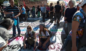 Protesters stand on banners laying on the ground during a demonstration in front of the Greek Parliament building in Athens, 06 November 2012.