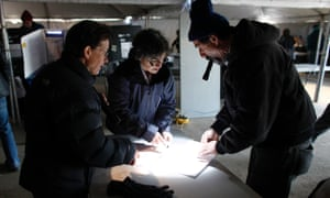 Election workers help a voter, right, finalize his  ballot at a makeshift polling station for residents of the storm-ravaged Rockaways, New York.