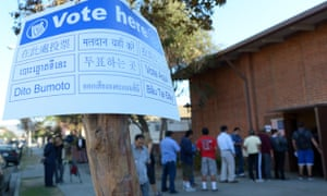 The voting sign shows the ethnic diversity of the area as Sun Valley residents wait in line to vote at Our Lady of The Holy Church.