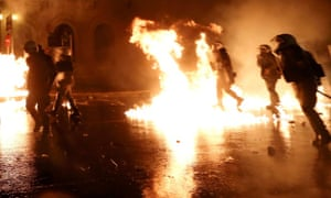 Burning issues: Flames from molotov cocktails flare up near Greek riot police during clashes with protestors at a 48-hour strike by the two major Greek workers unions in central Athens. Greek police fired teargas and water cannons to disperse thousands of protesters who flooded into the main square before parliament on Wednesday in a massive show of anger against lawmakers due to narrowly pass an austerity package.