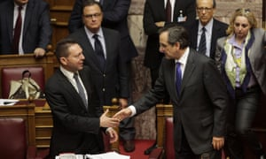 Greek Finance Minister Yannis Stournaras (L) shakes hands with Greek Prime Minister Antonis Samaras at the end of a session of the Greek parliament dedicated to new austerity measures, in Athens on November 7, 2012