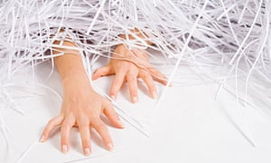 Young woman buried under shredded paper