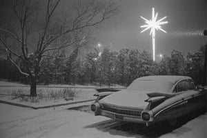 Joel Meyerowitz Monograph: A car is parked in snowy night with Christmas star behind
