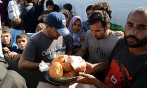 Syrian refugees receive food distributed by Turkey's Red Crescent at a makeshift refugee camp in the northern Syrian city of Qah in the Idlib province near the border with Turkey. More than 500 people have been coming to the camp on a daily basis as they flee deadly clashes between Syrian rebels and regime forces.