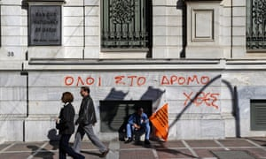 """A municipal worker participating in a anti-austerity rally sits in front of the National Bank of Greece building, underneath graffiti reading in Greek """"All to the streets yesterday"""", in central Athens, Friday, Nov. 9, 2012."""