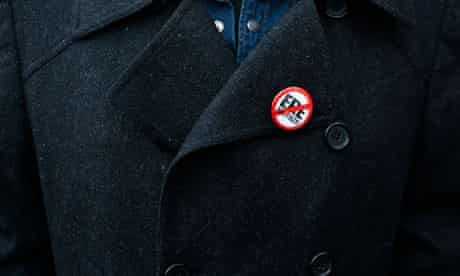 An El Pais newspaper employee wears a pin during a protest against lay-offs